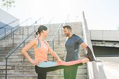 Latin Couple Stretching Together Outdoors. poster