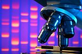 pic of genes  - Close up of laboratory microscope with DNA gel image background - JPG