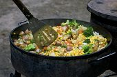foto of dutch oven  - stew being prepared in a large dutch oven outdoors - JPG
