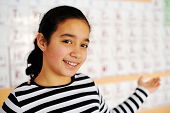 Cute lovely school children at class with periodic table of the elements poster