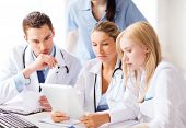 healthcare, medical and technology concept - group of doctors looking at tablet pc
