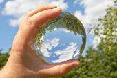 image of crystal glass  - In a held glass ball can you seen the landscape behind her - JPG