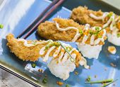 picture of masago  - Fried breaded ahi tuna resting on a ball of rice drizzled with masago mayonnaise and sprinkled with green onions and masago also known as capelin fish roe