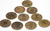 stock photo of brothel  - Closeup of a group of ten antique brass brothel and saloon tokens isolated on white - JPG