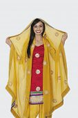 stock photo of dupatta  - Portrait of beautiful Indian woman in salwar kameez standing over gray background - JPG