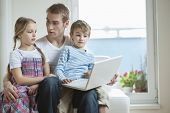 Father and children using laptop while sitting on chair
