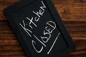 Miniature blackboard  - with 'kitchen closed' message handwritten in chalk - on rustic dark wood bac