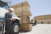 picture of logging truck  - African American male contractor using tablet PC while standing by logging truck - JPG