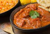 foto of curry chicken  - A delicious bowl of creamy chicken tikka masala with rice lemons and naan bread.