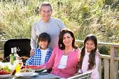 stock photo of 70-year-old  - Grandparents And Grandchildren Having Outdoor Barbeque - JPG