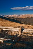 stock photo of split rail fence  - A split rail fence stands against the alpine tundra as the Colorado Rocky Mountains greet the days start in the early morning sunlight - JPG