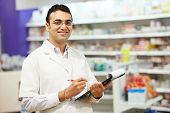 stock photo of antibiotics  - cheerful pharmacist chemist woman standing in pharmacy drugstore - JPG
