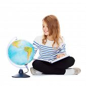 education and school concept - little student girl looking at globe and holding book