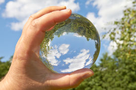 stock photo of oracle  - In a held glass ball can you seen the landscape behind her - JPG