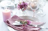 stock photo of tables  - Festive wedding table setting with pink flowers napkins vintage cutlery glasses and candles bright summer table decor - JPG