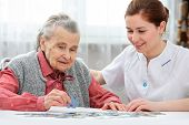 pic of geriatric  - Nurse helps the senior woman with a jigsaw puzzle to solve in a nursing home