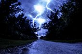 picture of lightning  - stunning lightning in a blue sky over a forest road - JPG