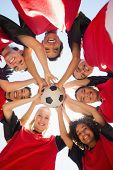 stock photo of united we stand  - Directly below shot of female soccer team with ball forming huddle against clear sky - JPG