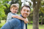 stock photo of shoulders  - Side view portrait of a father carrying young boy on back at the park - JPG