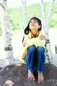 Picture of young biracial girl sitting on rock under trees.