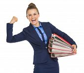 Smiling Business Woman With Stack Of Folders Showing Biceps