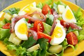 Salad With Anchovies On A Yellow Plate.