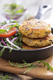 pic of veggie burger  - Vegan burgers with quinoa and vegetables served with arugula and salad - JPG