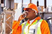 pic of substation  - african electrical engineer using cell phone in substation - JPG