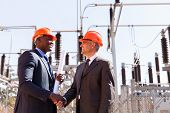 picture of substation  - two cheerful businessman handshaking in electric substation - JPG