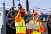 stock photo of substation  - technical workers discussing work at electrical substation - JPG