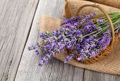 stock photo of wooden basket  - lavender flowers in a basket with burlap on the wooden background - JPG