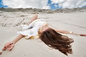 image of tunic  - Young pretty sexy woman in greek tunic lies on sand blindly - JPG