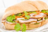 stock photo of duck breast  - Banh Mi - Crusty bread filled with smoked duck breast slices, carrot and daikon radish pickle (do chua) and green chilies, garnished with coriander. Vietnamese sandwich.