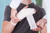 stock photo of bandage  - Nurse bandaging sprained wrist of young man - JPG
