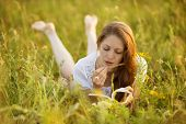 stock photo of beatitudes  - Beautiful girl with a book of wildflowers - JPG