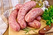 foto of sausage  - Raw pork sausage knife rosemary parsley oil garlic and checkered napkin on wooden boards background - JPG