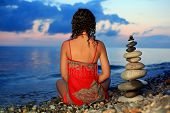 Beautiful Woman In Red Sundress Sitting Near To Pyramid From Pebble On Stone Seacoast In Evening