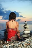 Beautiful Woman In Red Sundress Meditating Near To Pyramid From Pebble On Stone Seacoast In Evening