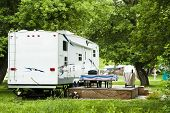 stock photo of trailer park  - Fifth Wheel camping trailers parked in a recreational vehicle campground - JPG