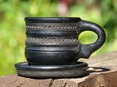 stock photo of loamy  - Old black arabian ceramic cup taken closeup on green background - JPG