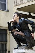 picture of pilaster  - sexy girl vampire with black leather coat outside during night on the top of pilaster building - JPG