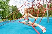 stock photo of leg-split  - Active girl sits on red ropes of playground in leg - JPG