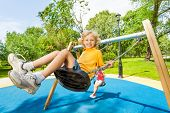 picture of swing  - Boy swings in opposite direction to the girl sitting calm on swings on the playground - JPG