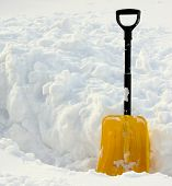 pic of snow shovel  - Yellow snow shovel standing on the snow - JPG