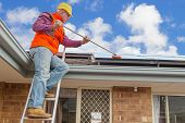 picture of cleaning house  - experienced worker cleaning solar panels on house roof - JPG