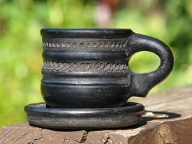 foto of loamy  - Old black arabian ceramic cup taken closeup on green background - JPG