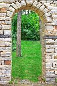 picture of old stone fence  - Old Limestone Stone Arch in Summer Garden - JPG