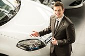 picture of showrooms  - Young man consultant in showroom is standing near car - JPG