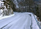 picture of slippery-roads  - dangerous curve of a frozen mountain road in winter - JPG