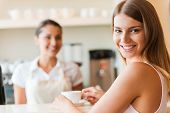 picture of over counter  - Beautiful young smiling woman holding coffee cup and looking over shoulder while female barista standing in the background - JPG